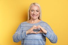 Portrait of mature woman making heart with her hands royalty free stock images
