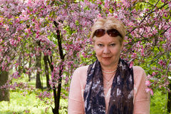 Portrait of mature woman near a decorative apple tree, which blo Stock Images