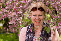 Portrait of mature woman near a decorative apple tree. Which bloom Royalty Free Stock Photo