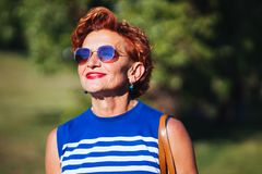 Portrait of a mature woman in the park. On a sunny day royalty free stock images