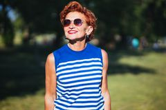 Portrait of a mature woman in the park. On a sunny day stock photo