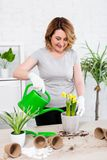 Portrait of mature woman planting and watering spring flowers at home. Portrait of attractive mature woman planting and watering spring flowers at home royalty free stock photography