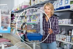 Portrait of mature woman purchasing bird cage in petshop. Mature woman purchasing bird cage in petshop Royalty Free Stock Image