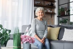 Pretty old lady sitting on sofa at living room royalty free stock image