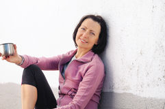 Portrait of mature woman resting after jog near the wall with cup in hand Royalty Free Stock Photos