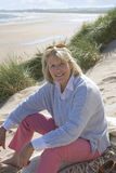 Portrait of mature woman sitting on beach royalty free stock photo