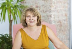 Mature woman sitting on chair in the living room stock photography
