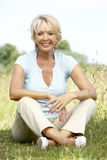 Portrait of mature woman sitting in countryside Royalty Free Stock Image