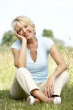 Portrait of mature woman sitting in countryside. Looking happy and relaxed Royalty Free Stock Images