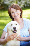 Portrait Of Mature Woman Sitting In Field With Dog Royalty Free Stock Images