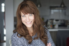 Portrait Of A Mature woman smiling at the camera. In the kitchen Stock Photos
