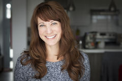 Portrait Of A Mature woman smiling at the camera. In the kitchen Stock Photo