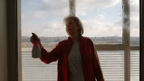 Portrait of mature woman sprays window cleaner on large window indoors - Front View stock video