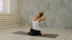 Portrait of mature woman stretching her neck and looking away at yoga class stock video