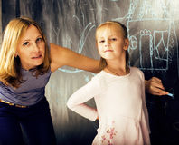 Portrait of mature woman teacher with little cute blonde girl pupil writing on blackboard together, lifestyle people Stock Images