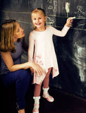 Portrait of mature woman teacher with little cute blonde girl pupil writing on blackboard together, lifestyle people Royalty Free Stock Photo