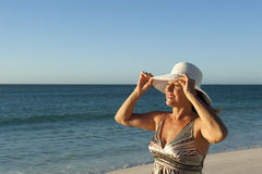 Portrait of mature woman with white hat at beach Stock Image
