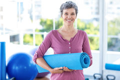 Portrait of mature woman with yoga mat Stock Images