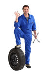 Portrait a mechanic. Resting foot on car tyre royalty free stock image