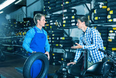 Portrait of mechanic and customer chatting about motorbike tires. Portrait of diligent positive mechanic and customer chatting about motorbike tires at service royalty free stock photos