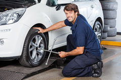 Portrait Of Mechanic Fixing Car Tire At Garage Royalty Free Stock Photography