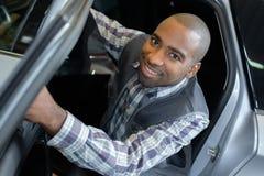 Portrait mechanic leaning out car. Portrait of mechanic leaning out of car Stock Photography