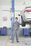 Portrait of Mechanic with Power Tool Next to Car Wheel, Looking At Camera Stock Image