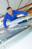 Portrait mechanic on roof camper van Royalty Free Stock Images
