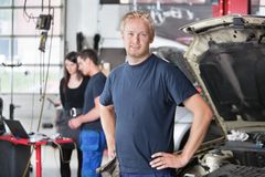 Portrait of Mechanic in Shop. Portrait of a  young mechanic in auto repair shop with customer in background Royalty Free Stock Photo