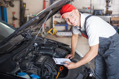Portrait of a mechanic. Taking notes and smiling royalty free stock images