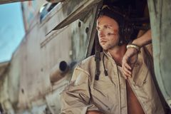 Portrait of a mechanic in uniform and flying near, standing under an old bomber airplane in the open air museum. Stock Images