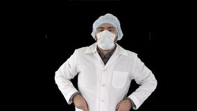Portrait of medical doctor putting mask and hat on, alpha channel stock footage