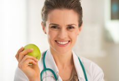 Portrait of medical doctor woman with apple. Portrait of smiling medical doctor woman with apple Stock Image