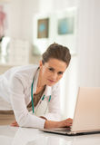 Portrait of medical doctor woman working on laptop Stock Photos