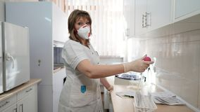 Portrait of medical laboratory technician in respirator and pipette with bulb