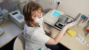Portrait of a medical laboratory technician in respirator with tube in a hand