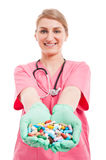 Portrait of medical nurse lady smiling showing lots of pills Stock Images