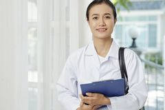 Medical professional visiting the patient. Portrait of medical professional standing in white coat holding blue folder and smiling at camera while standing near royalty free stock images