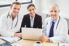 Portrait of medical team with laptop in conference room Stock Images