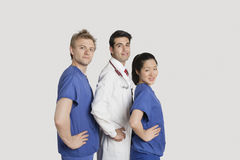 Portrait of medical team standing hands on hips over gray background Stock Images