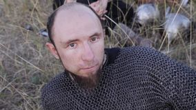 Portrait of a Viking dressed in chain mail lying on the grass stock video footage