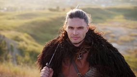 Portrait of Medieval Male Viking Warrior. In his hand a sword, wind blowing hair. Medieval Reenactment stock video