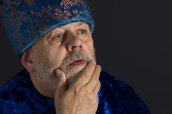 Portrait of meditating senior man in blue oriental clothes Stock Photo