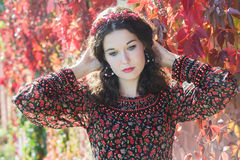 Portrait of melancholy autumn girl with autumn wreath at red floral background of grape woodbine Stock Images
