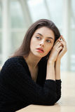 Portrait of melancholy young beautiful brunette woman in a black sweater on a light geometric blurry background Royalty Free Stock Photo