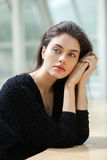 Portrait of melancholy young beautiful brunette woman in a black sweater on a light geometric blurry background Royalty Free Stock Image