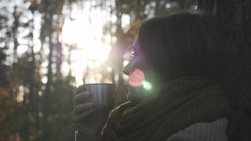 Portrait of melancholy young brunette woman tourist in cozy scarf relaxing in autumn forest, holding cup of hot tea and looking at. Sunset stock footage