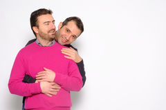 Portrait of a men gay couple in studio embracing Stock Images