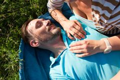 Portrait of man with woman hands on his chest. Smiling man laying on blue blanket and green grass with hands of girlfriend stock images