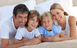Portrait of a merry family lying in a bed. Smiling at the camera Stock Image